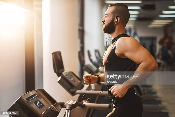 side view of a young athlete running on treadmill. - treadmill stock pictures, royalty-free photos & images