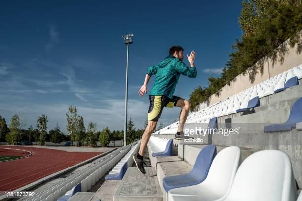 スタジアムの階段を走る若い男性アスリートのサイドビュー。爆発的なランニングトレーニング - トレーニングドリル ストックフォトと画像