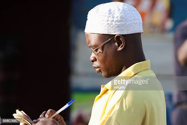 Side view of a young man writing in diary at Bamako Mali