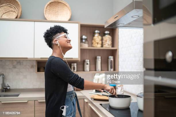 side view of a young woman cooking and listening music at home - pardo brazilian stock pictures, royalty-free photos & images