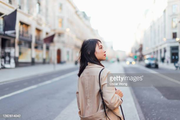 side view of a young woman exploring and discovering regent street, london - hope stock pictures, royalty-free photos & images