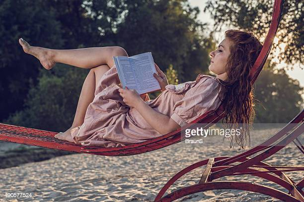 Vue latérale d'une jeune femme lisant un livre.