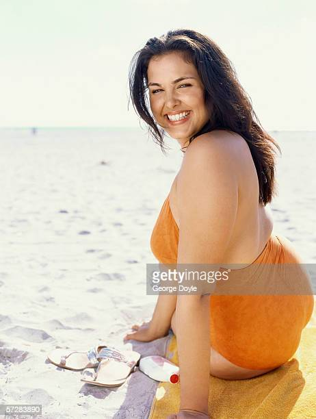 side view of a young woman sunbathing - fat woman at beach stock photos and pictures