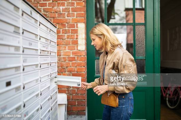 side view of active senior woman checking mailbox - mailbox stock pictures, royalty-free photos & images