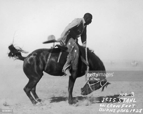 Side view of AfricanAmerican rodeo rider Jess Stahl riding atop his bucking horse Crow Foot at the Harney County Roundup Burns Oregon Stahl wears...