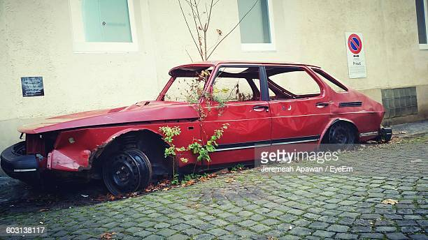 Side View Of An Abandoned Car Against Wall