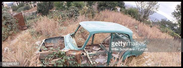 Side View Of An Abandoned Car On Landscape