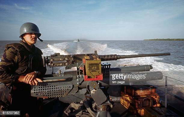 A side view of an American swift boat gunner on a river in the southern Delta