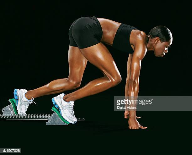 Side View of an Athlete Crouching in Starting Blocks