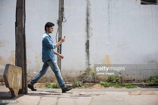 Side view of an Indian man walking along street.