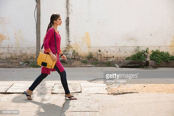 side view of an indian woman walking along street. - kurta stock pictures, royalty-free photos & images