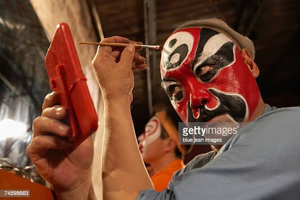 Side view of an old actor as he holds a mirror and carefully applies traditional Chinese face paint to his forehead.