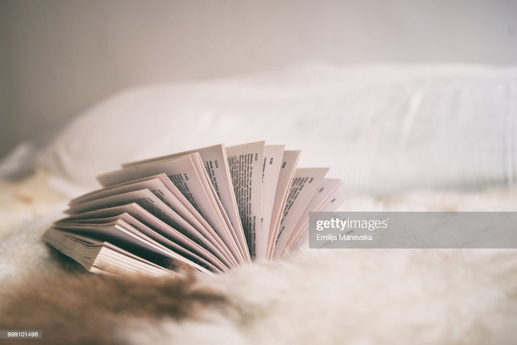 Side view of an open book lying on a bed : Stock Photo