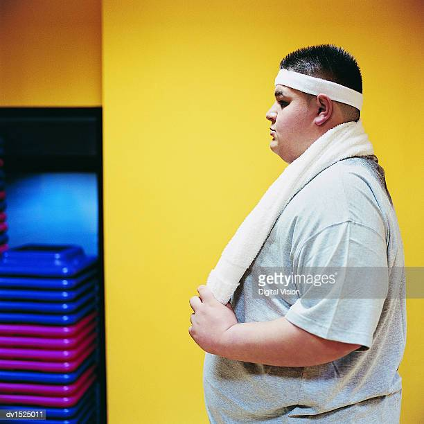 Side View of an Overweight Man Standing in the Gym