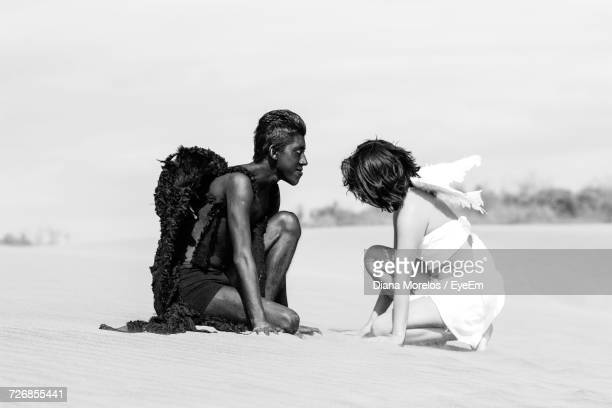Side View Of Angel And Devil Kneeling On Sand At Beach Against Clear Sky
