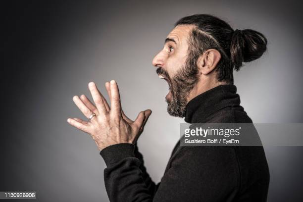 side view of angry man screaming while standing against gray background - mouth open stock pictures, royalty-free photos & images