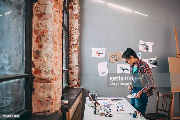 Side view of artist painting at table in art studio