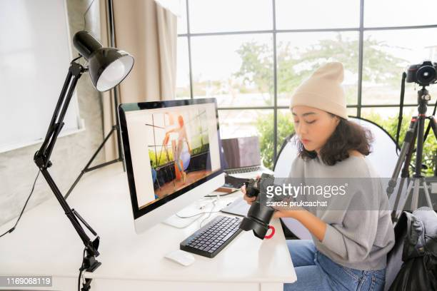 side view of asian female freelancer photographer cheking photos on a digital camera while sitting at the table in workstation - fotógrafo fotografías e imágenes de stock