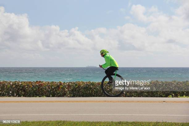 side view of athlete riding a unicycle near the beach - fauci stock pictures, royalty-free photos & images