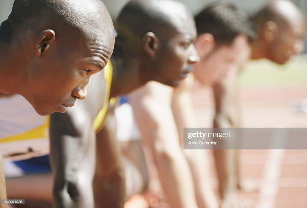 Side View of Athletes Crouching on the Starting Blocks of a Running Track : Stock Photo