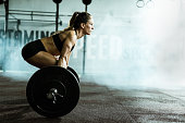 Side view of athletic woman exercising deadlift in a gym.