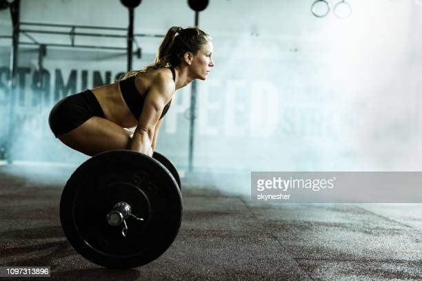 side view of athletic woman exercising deadlift in a gym. - crossfit stock pictures, royalty-free photos & images