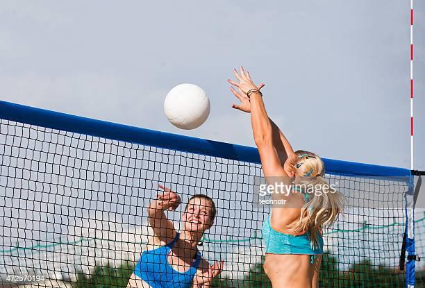 Vista lateral de atractiva voleibol playero acción en el Net