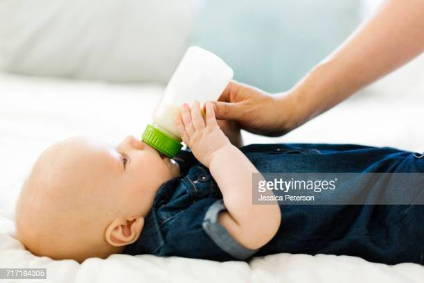 Side view of baby boy ( 12-17 months) being fed by woman with bottle of milk