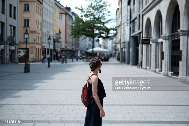 side view of backpack woman standing on street amidst buildings in city - figurantes incidentais - fotografias e filmes do acervo