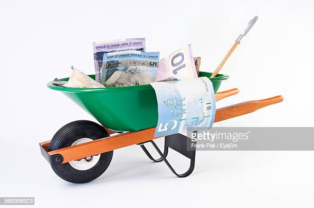Side View Of Banknotes In Wheelbarrow Over White Background