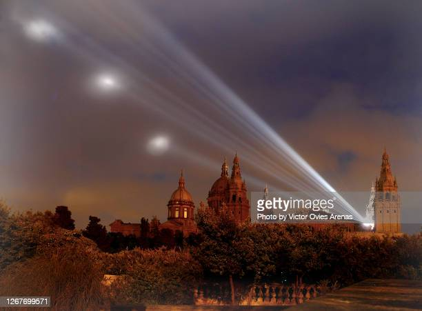 side view of barcelona's national palace from montjuic at night with its white light beams shining majestically in the sky - victor ovies fotografías e imágenes de stock