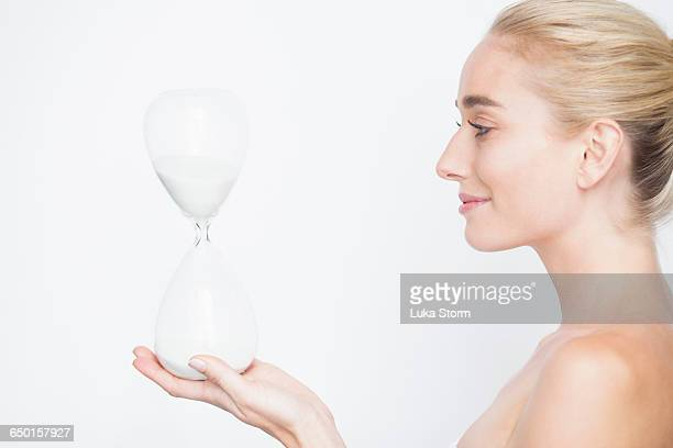 side view of bare shouldered woman holding hourglass smiling - beautiful bare women fotografías e imágenes de stock