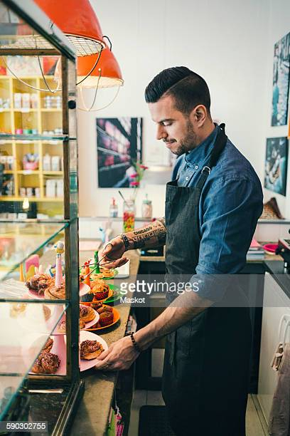 Side view of barista with pastries at cafe counter