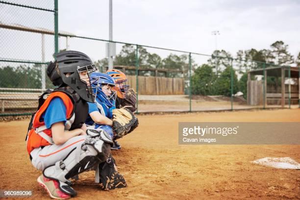 side view of baseball catchers crouching on field - receptor de béisbol fotografías e imágenes de stock