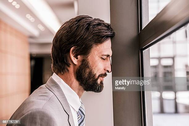Side view of bearded businessman, eyes closed, head leaning against window frame