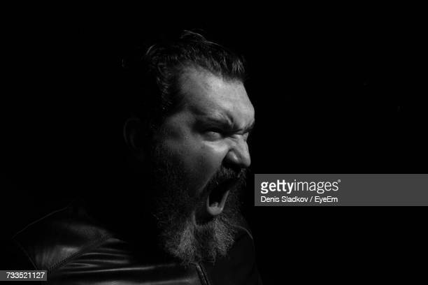 side view of bearded mid adult man screaming against black background - furioso foto e immagini stock