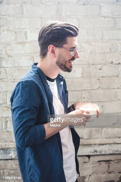 side view of bearded smiling computer programmer holding coffee cup while standing in office - fully unbuttoned stock pictures, royalty-free photos & images