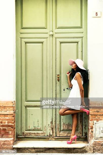 Side View Of Beautiful Mid Adult Woman Standing Against Old Closed Door