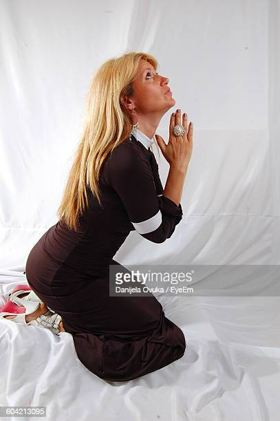 Side View Of Beautiful Woman Praying Against White Curtain