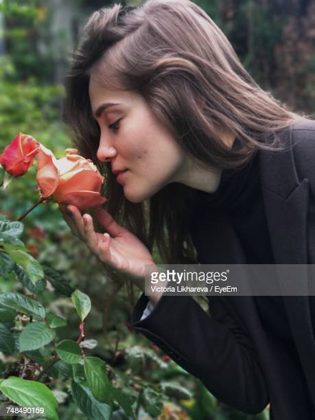 Side View Of Beautiful Woman Smelling Rose At Park