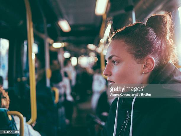 Side View Of Beautiful Woman With Hair Bun In Bus