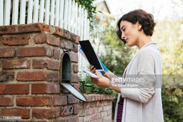 side view of beautiful young woman at mailbox - receiving stock pictures, royalty-free photos & images