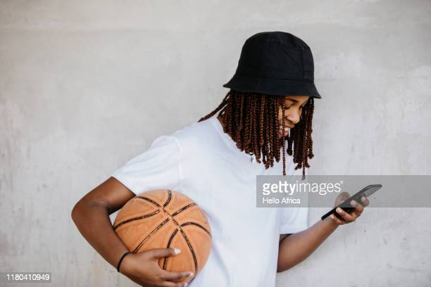 side view of beautiful young woman reading her phone with basketball under arm - sporting term stock-fotos und bilder