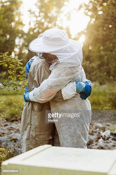 Side view of beekeepers embracing on field