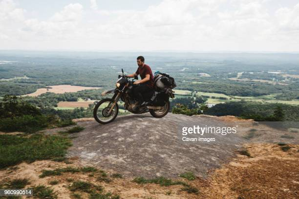side view of biker riding motorcycle on mountain against sky - ecchi biker stock pictures, royalty-free photos & images