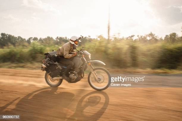 side view of biker wearing crash helmet while riding motorcycle on dirt road against sky - ecchi biker stock pictures, royalty-free photos & images