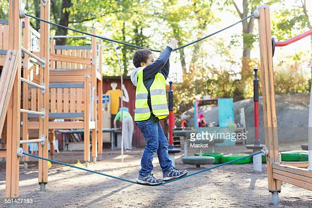 side view of boy balancing on rope at playground - incidental people stock pictures, royalty-free photos & images