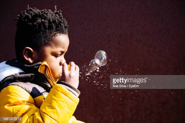 Side View Of Boy Blowing Bubbles