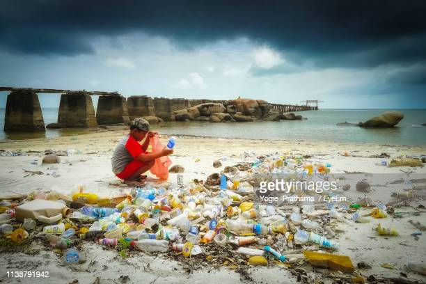side view of boy cleaning garbage while crouching at beach against cloudy sky - プラスチック ストックフォトと画像