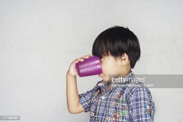 Side View Of Boy Drinking Water In Glass Against Wall